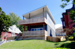 View of contemporary designed multi-story home with angled balconies on a rising hill.