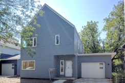 Exterior view of a home being renovated. Contemporary design of two story home with blue siding.