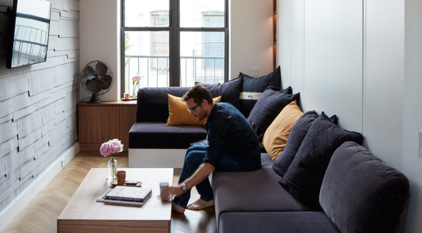 image of man sitting on a couch in a small, modern apartment